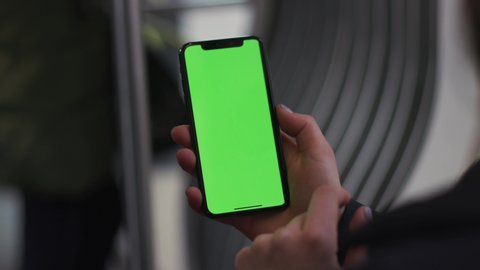 NEW YORK - 5 April 2018: Slow motion woman hands use touch holding a mobile telephone with a vertical green screen in tram chroma key smartphone technology cell phone street touch message display