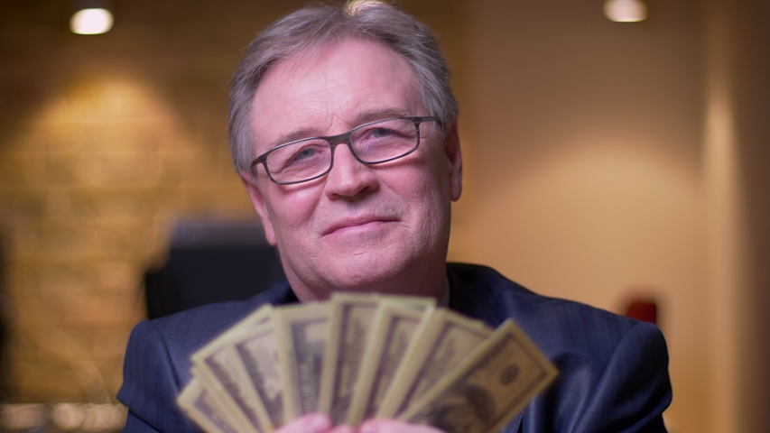 Portrait of senior businessman in formal costume counting money being glad and satisfied in office. | Shutterstock HD Video #1029977591