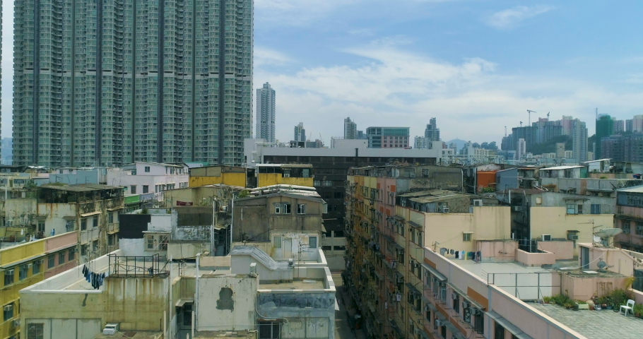 Drone rises above the old last century residential area of Hong Kong. Revealing a panorama of a modern shina city with a dense building and skyscrapers. Aerial View. 4K | Shutterstock HD Video #1029987071