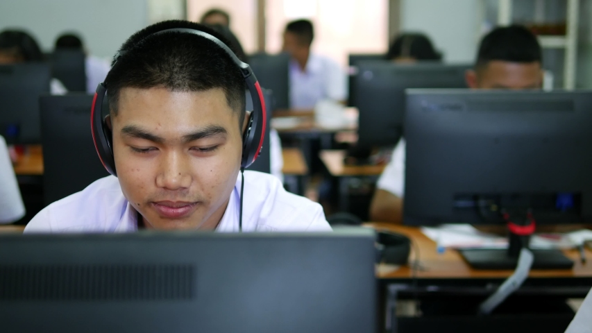 Asian high school male students wearing headphones are laughing and enjoying social media in computer class.   Shutterstock HD Video #1029995411