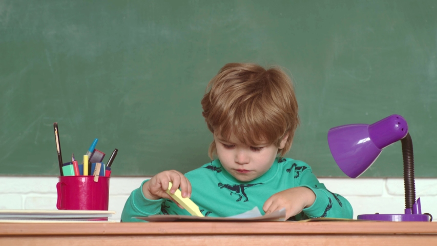 Schoolboy with lesson. Happy smiling pupils drawing at the desk. Kid is learning in class on background of blackboard. School kids against green chalkboard   Shutterstock HD Video #1030042511