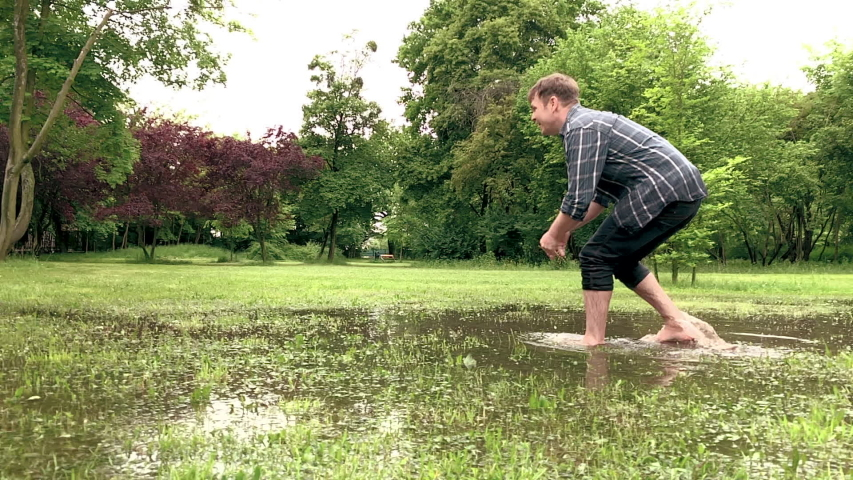 Slow Motion. Australian Shepherd Dog with owner playing on green grass at park. Happy barefoot Man and wet Aussie run on watery meadow after rain, water sprinkles. Dog and people enjoy at outdoors.   Shutterstock HD Video #1030075331