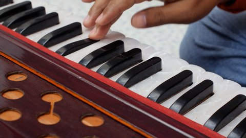 Closeup shot of hands of musician playing keys of harmonium.