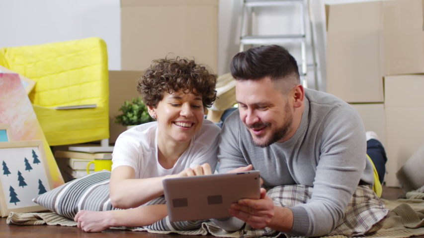 Panning full shot of relaxed middle-aged Caucasian couple lying on their stomach with cushions on floor of their new home and planning house renovations, while ordering goods online on tablet   Shutterstock HD Video #1030096511