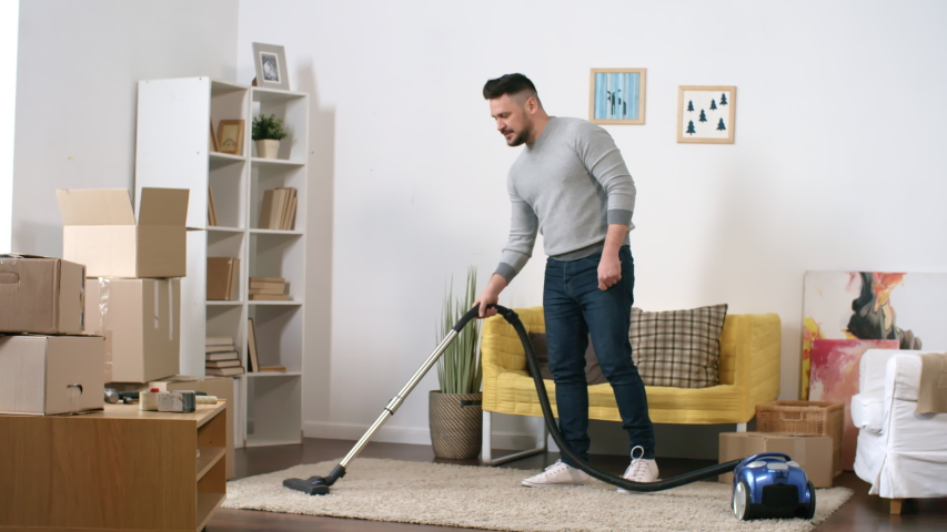 Full shot of 30-something cheerful Caucasian man tidying up his new home after relocation, vacuuming carpet in living room and smiling to himself, with some unpacked moving boxes lying around   Shutterstock HD Video #1030103531