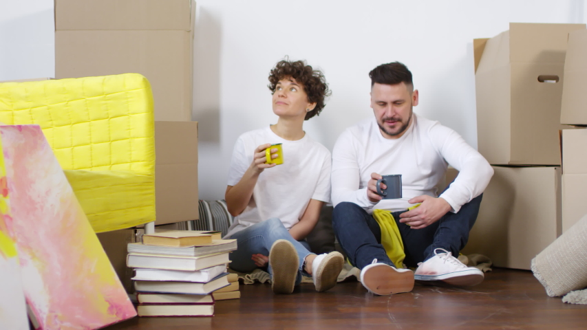 Full shot of young Caucasian couple sitting on floor against wall in their new home, surrounded by cardboard boxes, books and furniture, relaxing, chatting to each other and drinking tea   Shutterstock HD Video #1030105481