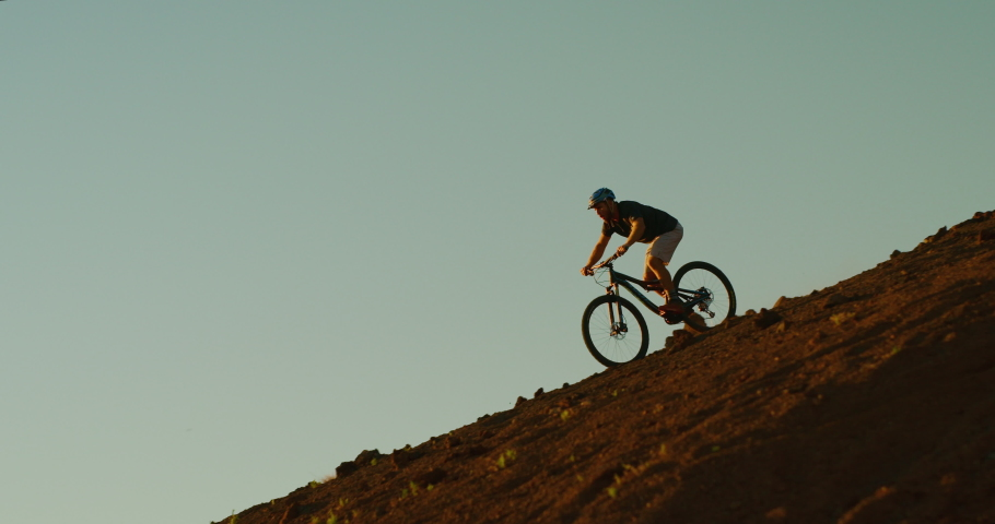 Epic mountain biking adventure, extreme mountain biker riding steep downhill fast, shredding dusty turns at sunset in the clouds #1030129481