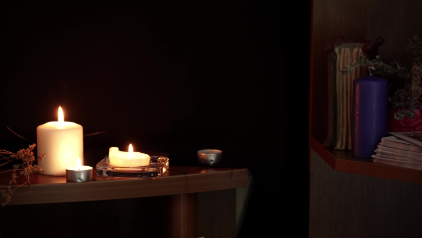 Composition of esoteric objects used for healing, meditation, relaxation and purifying. White candles, glass ball and open book on table on a black background. Occult, esoteric and divination concept. | Shutterstock HD Video #1030171031
