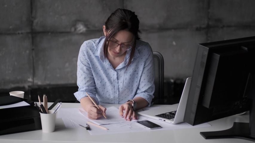 Young woman working at the table in the office in the style of a loft. | Shutterstock HD Video #1030199921