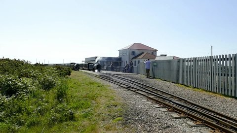 Dungeness Kent England May 2019. Romney, Hythe and Dymchurch 15 in gauge train pulling out of Dungeness Station with carriages attached. One other train stationary alongside.