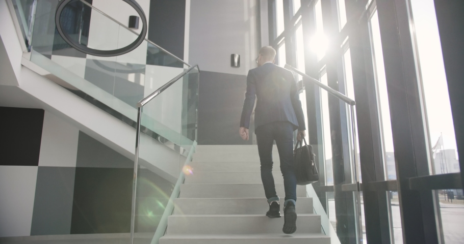 Office manager walking up on the stairs go to his cabinet in the upstairs the building | Shutterstock HD Video #1030207241