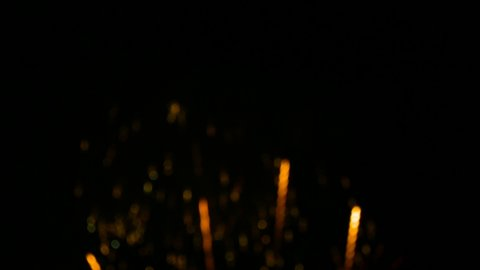 4K. fireworks background. abstract blur of real golden shining fireworks with bokeh lights in the night sky. glowing fireworks show. New year's eve fireworks celebration