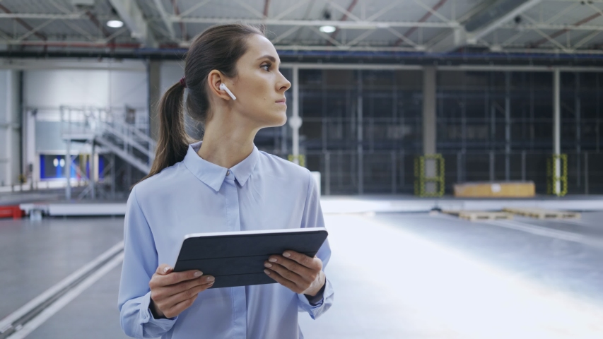 Female worker talking with colleague and checking product quantity in factory | Shutterstock HD Video #1030246991