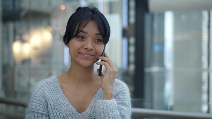 Pan shot slow motion of funny happy black hair asian female wearing grey sweatshirt talking on phone while walking. Business center | Shutterstock HD Video #1030267331