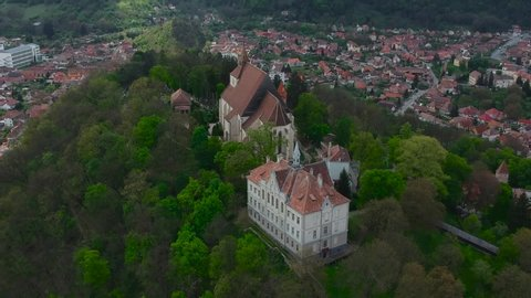 Drone Aerial of Evangelical Church and Liceul Teoretic Joseph Haltrich High School Surrounded With Forest Park on Hill of Sighisoara City Transylvania Romania