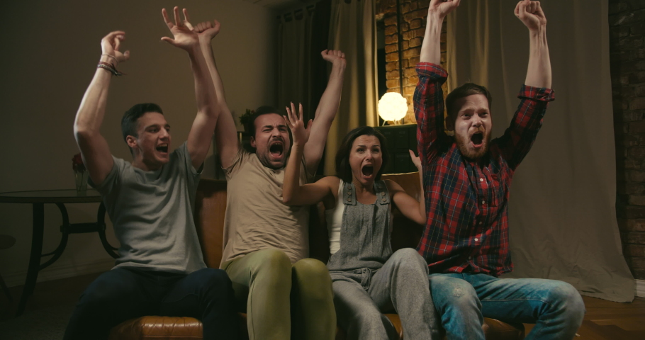 One female and three male friends watch football on TV at home. Their favourite team wins, company is happy, shouts and hugs all together