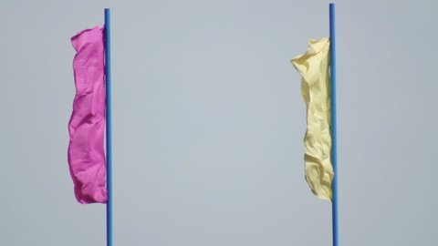 Multicolored festive flags evolve in the wind against a blue sky, background, festive, slow motion