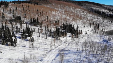 Drone shot of hills at heber valley and motor sleds on rural roads this  video shows family on snowmobiles riding on the snowy forest road