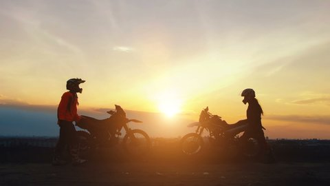 Silhouettes two riders with their bikes greet each other with victory. Silhouettes of motorcycles and riders on the background of beautiful sunset. Enjoy the freedom. Enduro.