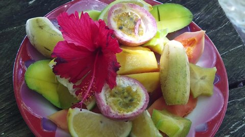 SLOW MOTION: fresh local fruit dish at Anse Source d'Argent, La Digue. Healthy exotic summer diet on tropical beach at Seychelles.