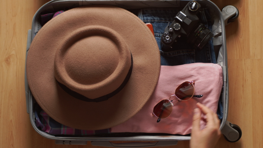 Faceless female hands packing trunk bag for travel slow motion 4k close up. Top view of unrecognizable woman putting clothes gadget devices hat sun glasses into suitcase ready for trip. Tourism summer | Shutterstock HD Video #1030364981