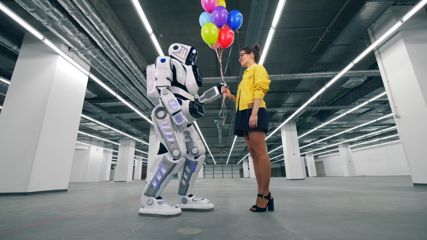 A girl gifting colorful balloons to her friend robot. | Shutterstock HD Video #1030374371