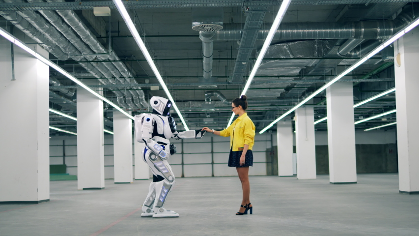 A robot walks towards a woman and takes her hand. | Shutterstock HD Video #1030374431