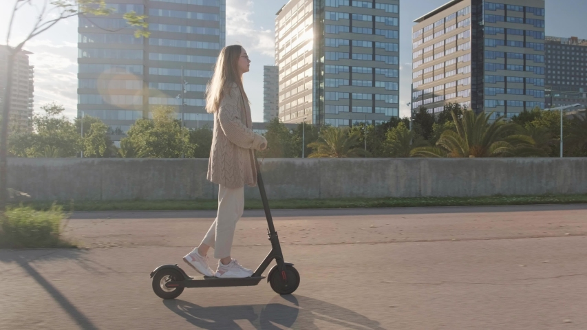 Young beautiful woman riding an electric scooter to work, modern girl, new generation, electric transport, ecology, ecological transport, sunset, electric skateboard, 4k | Shutterstock HD Video #1030375331