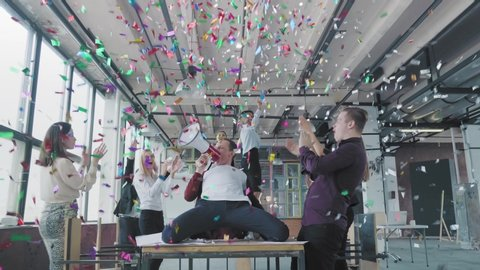 Manager start to dance on the table, sings into a megaphone, accelerates and slide on lap. Colleagues blow up flappers with confetti. Office celebration. Success. Corporate party business team