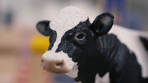 Plastic miniature cow with toys around