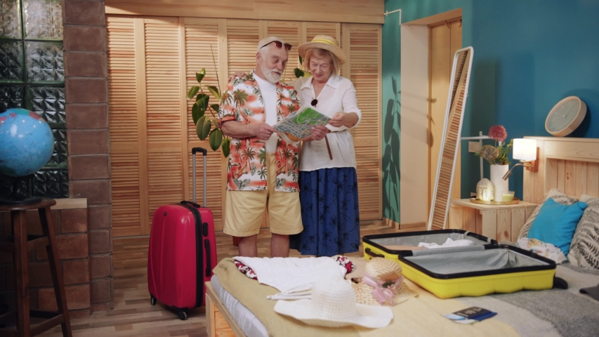 Happy mature couple with luggage looking hold maps talk going on holiday senior suitcase together caucasian holiday bag elderly family girl home mature older pensioner tourism travel trip slow motion | Shutterstock HD Video #1030450061