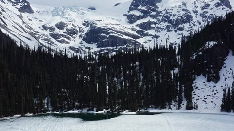 Aerial drone pedestal up ascending shot showing the trees and snow-covered mountains in the Joffre Frozen Lake in Pemberton, British Columbia, Canada.