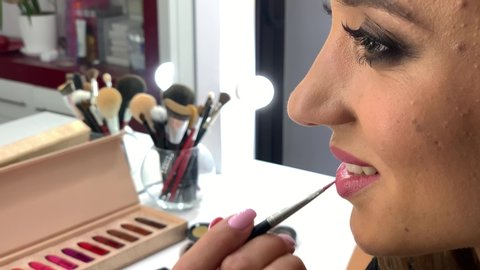 Makeup. Close Up slow motion footage of professional makeup artist applying makeup on models face before fashion show