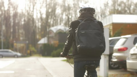 Back view of young commuter with a backpack riding to work by bike. Employee in casual clothes living a healthy life and choosing eco-friendly traveling in the city.