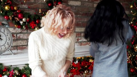 Slow motion of two attractive women in warm desses and stockings dancing in Christmas decorations