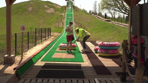 """""""AB park"""" attraction place in the region of Lielvarde, Latvia - May of 2019.  Young people with an inflatable camera sliding. The attraction with water slide rings."""