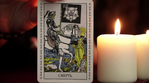 KRASNODAR, RUSSIA - 20 FEBRUARY 2019: A witch is fortune teller in black robe shows tarot card. White candles on table. Occult, esoteric, divination and wicca concept. Translation: The Death Man.