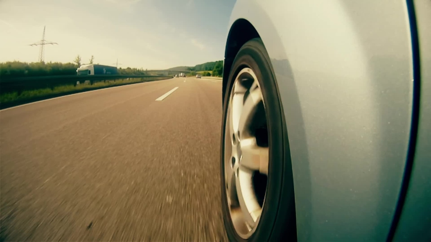 A highly stylized clip of a car speeding down the highway on the German autobahn. Highway wheel strong grade.