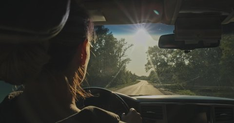Woman drives the car while sunset.  Young woman driving the car.  Young adult girl driving car. Real time. Sun's rays shine through the windshield of the car. Rear View to woman drives a automobile