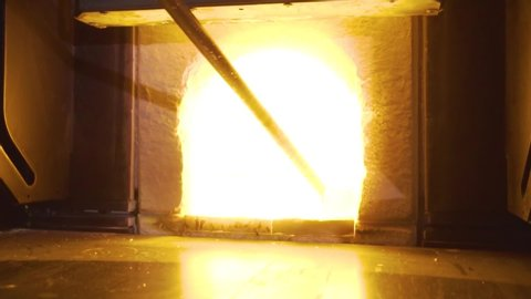 Glassblower in his workshop taking the rod with liquid glass out of glowing hot oven.