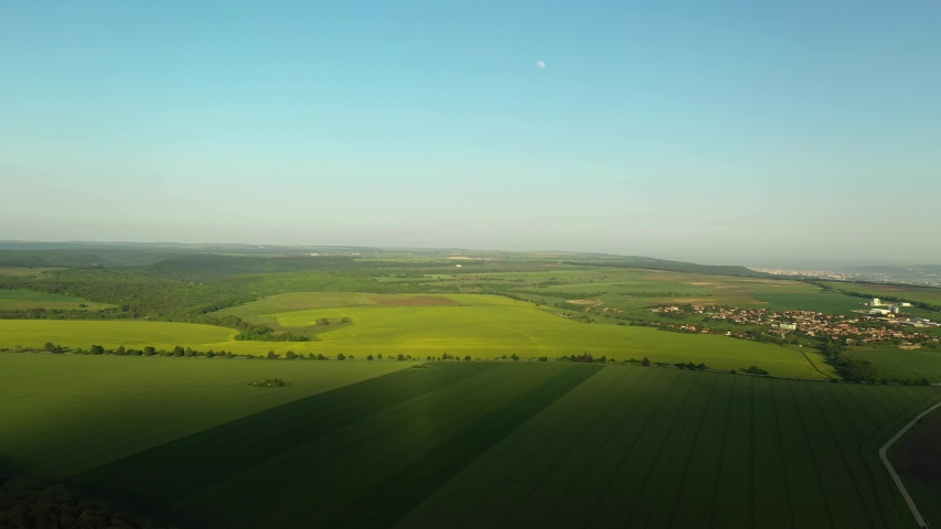Aerial Descent Over Green Fields with Clear Blue Sky, Moon, Road and Small Town in the Background #1030618301