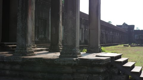 Sliding view of young woman coming on the porch of Angkor Wat temple and taking picture on her smartphone. The temple was built in 12th century in Cambodia and dedicated to Vishnu. Cambodia