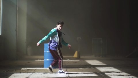 Glowing neon lines modern colorful illumination. Professional young asian hip-hop male dancer in sport wear dancing in the dark abandoned building in front of blue gas barrel. Contemporary. Hip hop