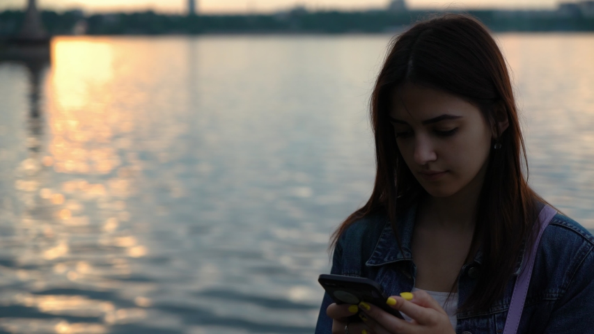 Lonely and calm caucasian girl standing on the quay with smartphone in hands and surfing in social nets | Shutterstock HD Video #1030676231