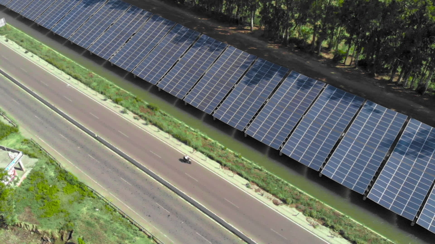 Aerial view of photovoltaic Solar Panel power station next to the highway located on Canal surrounding Agricultural field near road on which pass cars. Drone Aerial view video of solar power plant