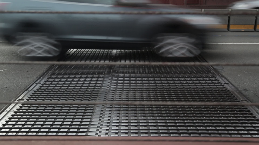 Cars drive across the bridge and over a metal grate on the freeway. | Shutterstock HD Video #1030721441