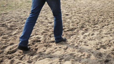man in blue jeans walks in the sand close-ups of the coast of the Baltic Sea