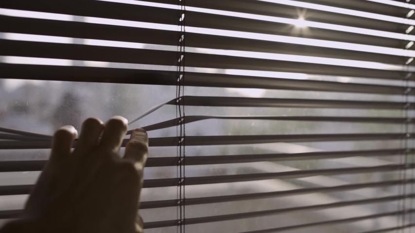Pulling down on a window blind or shutter in order to look outside | Shutterstock HD Video #1030751651
