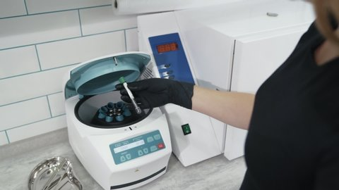 Close up doctor hands puts test tube in plasma lifting centrifuge, slow motion. Preparation of blood for injections