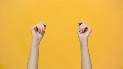 Woman hands snaps her fingers to music rhythm gesture isolated over yellow background in studio. Copy space for advertisement. With place for text or image. Advertising area, mock up.